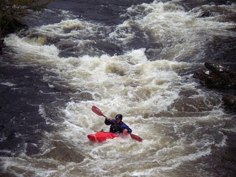 White water kayaking: A kayaker on a white water rapid.