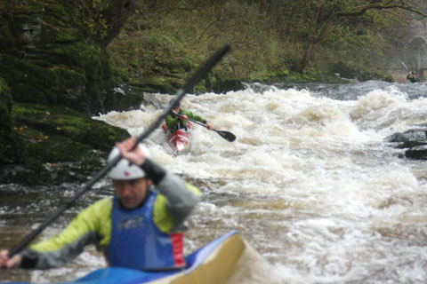 Wild Water Racing. Two wild water kayakers race on a white water river rapid.
