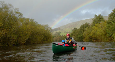 What's the difference between a canoe and a kayak? Image shows a man and boy in an open canoe