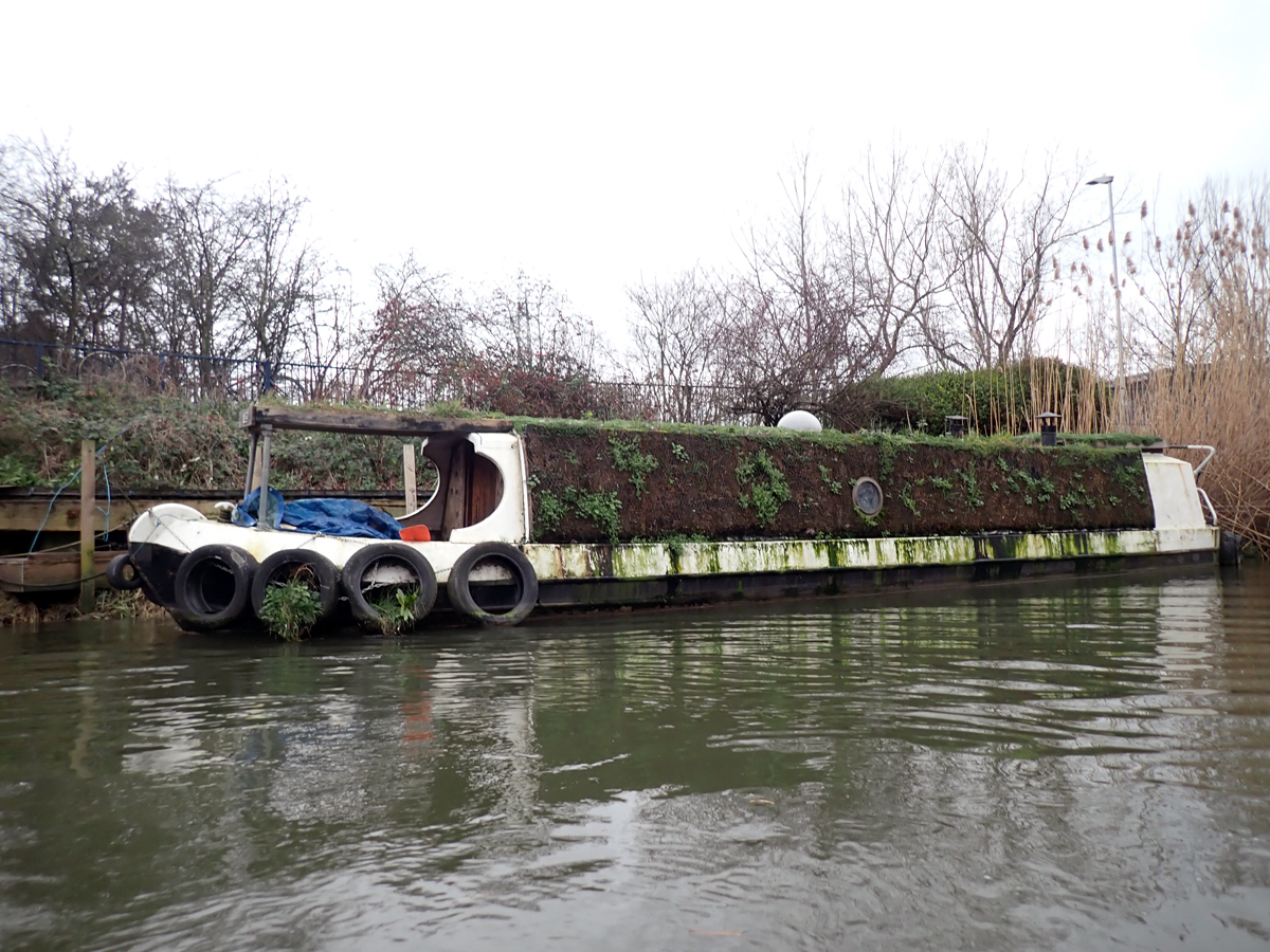 A barge with green, living walls and roof